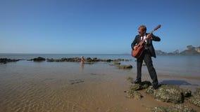 El guitarrista juega en muchacha de la playa se sienta emocionalmente en roca en el mar almacen de video