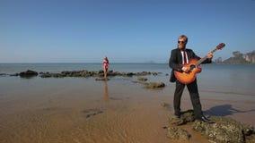 El guitarrista juega principal en roca en la playa para la muchacha rubia almacen de metraje de vídeo