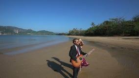 el guitarrista juega y la muchacha rubia liga la presentación en marea baja almacen de metraje de vídeo