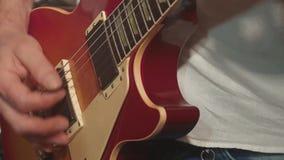 El guitarrista toca la guitarra como parte de una banda, en un concierto metrajes