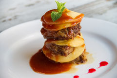 El hígado de becerro con las manzanas puso capas con la salsa en una placa blanca Imagen de archivo libre de regalías
