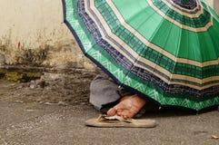 El habitante inidentificable de la calle duerme debajo del paraguas en el pavimento imágenes de archivo libres de regalías