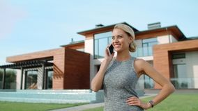 El hablar acertado de la mujer móvil cerca de casa de lujo Mujer feliz que llama el teléfono almacen de metraje de vídeo