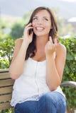 El hablar adolescente de risa en el teléfono celular al aire libre en banco Imagenes de archivo