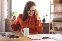El hablar auxiliar de la oficina en el teléfono imagen de archivo