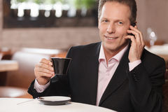 El hablar con el socio comercial. Coffe de consumición del hombre de negocios alegre Fotografía de archivo