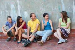 El hablar de cinco personas jovenes Imagenes de archivo