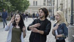 El hablar de los amigos al aire libre en la calle urbana pública asombrosamente que tiene una reacción asustada almacen de video