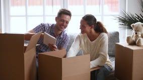 El hablar de risa de los pares jovenes felices desempaquetando las cajas de cartón abiertas juntas almacen de metraje de vídeo