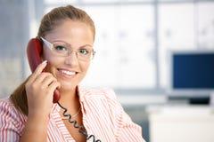 El hablar de trabajo del recepcionista bonito en el teléfono Imagen de archivo