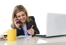 El hablar de trabajo rubio caucásico feliz de la mujer de negocios en el teléfono móvil Imágenes de archivo libres de regalías