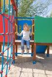 El hablar del niño ascendente en diapositiva en patio Fotografía de archivo libre de regalías
