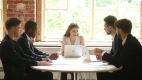 El hablar ejecutivo femenino con los empleados de sexo masculino diversos en la reunión de la oficina almacen de metraje de vídeo