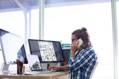 El hablar ejecutivo masculino en el teléfono móvil mientras que trabaja en su escritorio Foto de archivo libre de regalías