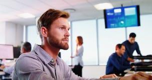 El hablar ejecutivo masculino en el teléfono mientras que trabaja en el escritorio