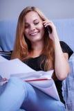 El hablar en el teléfono durante el aprendizaje Imagen de archivo libre de regalías