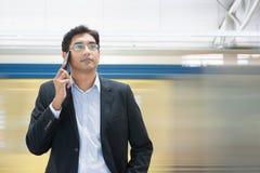 El hablar en el teléfono en la estación de tren Fotografía de archivo libre de regalías
