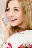 El hablar en la mujer rubia joven encantadora sonriente feliz móvil del teléfono celular que miente en la cama que sostiene la al Imagenes de archivo