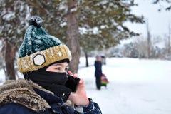 El hablar en el muchacho del teléfono en un sombrero hecho punto con un bubón y un pasamontañas imagen de archivo libre de regalías