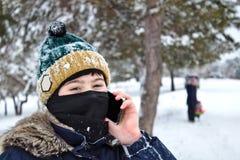 El hablar en el muchacho del teléfono en un sombrero hecho punto con un bubón y un pasamontañas foto de archivo