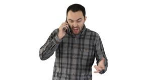 El hablar enojado del hombre en el teléfono y el caminar en el fondo blanco foto de archivo