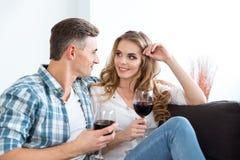 El hablar feliz de los pares y vino de consumición que se sientan en el sofá Fotografía de archivo libre de regalías