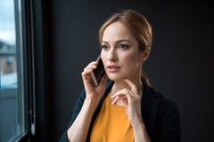 El hablar femenino alarmado por el móvil foto de archivo