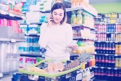 El hablar femenino de risa en el teléfono sobre compras Imagenes de archivo