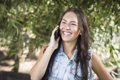 El hablar femenino joven de la raza mixta en el teléfono celular afuera Imagen de archivo libre de regalías
