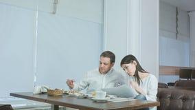 El hablar femenino joven en el teléfono durante almuerzo y el pedir su compañero de trabajo masculino ayuda metrajes