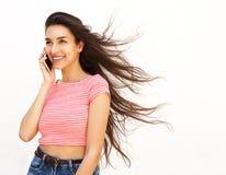 El hablar femenino joven sonriente en el teléfono celular Fotografía de archivo