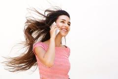 El hablar femenino joven sonriente en el teléfono móvil Fotografía de archivo