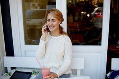 El hablar femenino sonriente en el teléfono de célula mientras que espera a su amigo en restaurante cómodo Foto de archivo