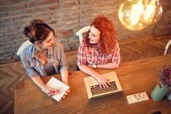 El hablar femenino y trabajo en el ordenador portátil Fotografía de archivo libre de regalías