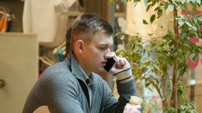 El hablar hermoso joven en el teléfono móvil y consumición del helado en el café Foto de archivo libre de regalías