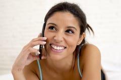 El hablar hispánico hermoso joven de la mujer relajado en el teléfono móvil en cama Foto de archivo libre de regalías