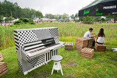 El hablar joven de los pares al aire libre cerca del piano viejo en el partido de la juventud fotos de archivo
