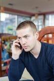 El hablar masculino joven en el teléfono Fotos de archivo