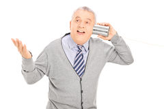 El hablar mayor a través de un teléfono de la lata fotos de archivo libres de regalías