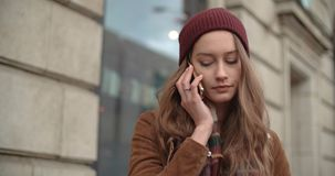 El hablar moreno hermoso en el teléfono en una ciudad Foto de archivo