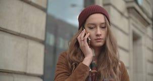El hablar moreno hermoso en el teléfono en una ciudad almacen de metraje de vídeo