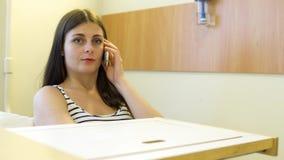 El hablar paciente de la chica joven en el teléfono en un cuarto de hospital almacen de video
