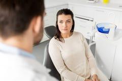 El hablar paciente femenino con el dentista en la clínica dental fotos de archivo