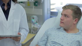 El hablar paciente masculino con el personal médico en sala de urgencias almacen de video