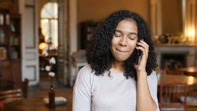 El hablar que camina afroamericano joven de la mujer negra en el teléfono celular en café metrajes