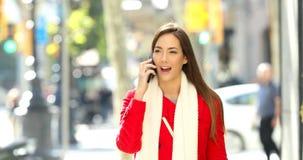 El hablar que camina de la mujer en el teléfono en la calle