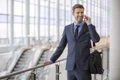 El hablar que camina permanente del hombre de negocios en su teléfono celular fotografía de archivo