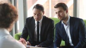 El hablar que escucha de los patrones serios de los hombres de negocios con el candidato en la entrevista de trabajo almacen de video