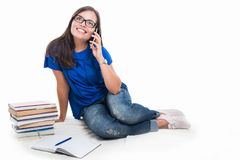 El hablar que se sienta de la muchacha del estudiante en el teléfono Foto de archivo