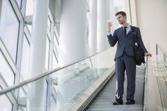 El hablar que se sienta del hombre de negocios en el teléfono celular mientras que en la escalera móvil foto de archivo